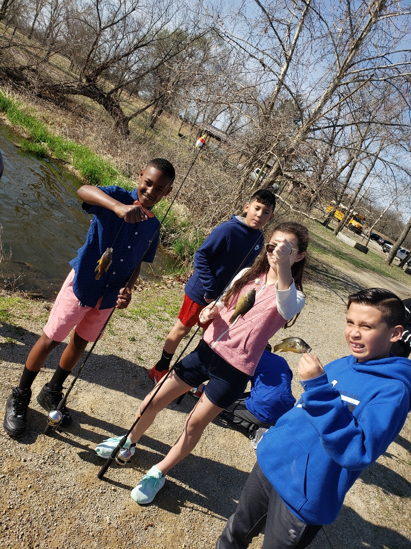 4 students with fishing poles and fish